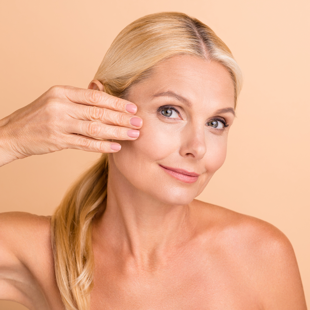 Woman with fresh skin and hand on her cheek